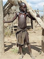 A young Kwegu girl stands among dry wood poles at her family's home.Adopting the practice of Karo women and girls, many Kwegu girls pierce a hole below the lower lip in which they place a thin piece of metal or a nail for decoration.The Kwegu known to the Karo as Muguji, a degoratory name meaning Working Ant, are the smallest tribe living on the banks the Omo River in southwest Ethiopia. Stock Photo - Premium Rights-Managednull, Code: 862-03820507