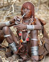 A Hamar woman blows a tin trumpet at a Jumping of the Bull ceremony.The Hamar are semi nomadic pastoralists of Southwest Ethiopia whose women wear striking traditional dress and style their red ochred hair mop fashion.The Jumping of the Bull ceremony is a rite of passage for young men. Stock Photo - Premium Rights-Managednull, Code: 862-03820511