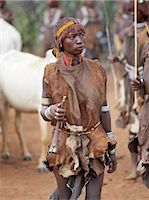 A Hamar woman holds a tin trumpet at a Jumping of the Bull ceremony.The Hamar are semi nomadic pastoralists of Southwest Ethiopia whose women wear striking traditional dress and style their red ochred hair mop fashion.The Jumping of the Bull ceremony is a rite of passage for young men. Stock Photo - Premium Rights-Managednull, Code: 862-03820512