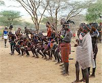 With whipping sticks in their hands, men crouch as they bless an initiate who is about to perform his Jumping of the Bull ceremony.The Hamar are semi nomadic pastoralists of Southwest Ethiopia who embrace an age grade system that includes several rites of passage for young men. Stock Photo - Premium Rights-Managednull, Code: 862-03820518