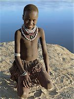 A young Nyangatom girl on the banks of the Omo River.The Nyangatom are one of the largest tribes and arguably the most warlike people living along the Omo River in Southwest Ethiopia. They form a part of the Ateger speaking people a cluster of seven eastern Nilotic tribes to which the Turkana of Northern Kenya and the Karamajong of Eastern Uganda belong. Stock Photo - Premium Rights-Managednull, Code: 862-03820542