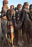 A group of Nyangatom girls and women with beautifully decorated leather skirts gather to dance.The Nyangatom are one of the largest tribes and arguably the most warlike people living along the Omo River in Southwest Ethiopia. Stock Photo - Premium Rights-Managednull, Code: 862-03820543