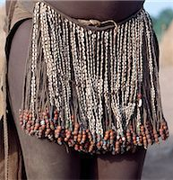 The decorated leather apron or skirt of a young Nyangatom girl. The numerous white discs woven into the strands of braided leather are made of ostrich shell.The Nyangatom are one of the largest tribes and arguably the most warlike people living along the Omo River in Southwest Ethiopia. Stock Photo - Premium Rights-Managednull, Code: 862-03820547