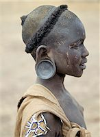 The typical hairstyle of a young Mursi girl.The Mursi speak a Nilotic language and have affinities with the Shilluk and Anuak of eastern Sudan.They live in a remote area of southwest Ethiopia along the Omo River, the countrys largest river. Stock Photo - Premium Rights-Managednull, Code: 862-03820568