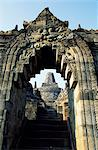 View to Grand Stupa from lower terrace through sculpted archway, Borobodur temple, Java, Indonesia.Ranking with Pagan and Angkor as one of the greatest Southeast Asian monuments, Borobodor is an enormous construction standing majestically on a hill overlooking lush green fields and distant hills, 42km northwest of Yogyakarta. Stock Photo - Premium Rights-Managed, Artist: AWL Images, Code: 862-03820595