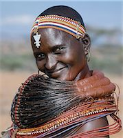 A Samburu woman wearing a mporro necklace, which denotes her married status. These necklaces were once made of hair from giraffe tails but nowadays, the fibres of doum palm fronds, Hyphaene coriacea, are used instead.The red beads after which the necklace is named are wound glass beads made in Venice c.1850. Stock Photo - Premium Rights-Managednull, Code: 862-03820645
