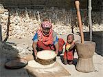 A Swahili woman winnows grain outside her home while her young son grasps a large pestle and mortar beside her.Her house, like most others in the village, is made of coral rag.The chequered history of Faza dates back several hundred years.