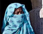 A Nubian woman, her face covered by her headscarf to denote her Muslim belief, stands outside the verandah of her home.The style of verandah arch is typical of the Nubian people.