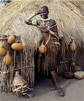 A Datoga woman relaxes outside her thatched house.The traditional attire of Datoga women includes beautifully tanned and decorated leather dresses and coiled brass armulets and necklaces.The Datoga live in northern Tanzania and are primarily pastoralists. Stock Photo - Premium Rights-Managednull, Code: 862-03821002