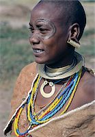 A Datoga woman in traditional attire, which includes beautifully tanned and decorated leather dresses and coiled brass necklaces and ear ornaments.Extensive scarification of the face with raised circular patterns is not uncommon among women and girls. Stock Photo - Premium Rights-Managednull, Code: 862-03821020