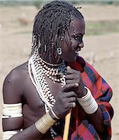 A Datoga young man in traditional attire.His braids are embellished with beads and aluminium can openers.Many of his white plastic bracelets are beautifully decorated with abstract and geometrical designs; long ago these bracelets would have been made of ivory. Stock Photo - Premium Rights-Managednull, Code: 862-03821021