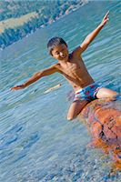 boy riding log in lake Stock Photo - Premium Royalty-Freenull, Code: 673-03826306