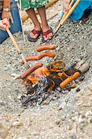 hot dogs roasting over beach fire Stock Photo - Premium Royalty-Freenull, Code: 673-03826323