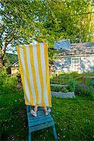 boy on garden chair under beach towel Stock Photo - Premium Royalty-Freenull, Code: 673-03826362