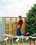 Man building a fence in a garden, Skane, Sweden. Stock Photo - Premium Royalty-Free, Artist: AWL Images, Code: 6102-03826891