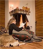 sweater and fireplace - A woman reading a book in front of a fireplace, Sweden. Stock Photo - Premium Royalty-Freenull, Code: 6102-03826955