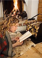 sweater and fireplace - A woman reading infront of  a fireplace, Sweden. Stock Photo - Premium Royalty-Freenull, Code: 6102-03826956