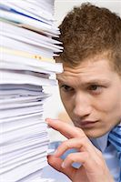 A man with a pile of paper in an office. Stock Photo - Premium Royalty-Freenull, Code: 6102-03827256