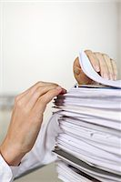 Two hands browsing through a pile of paper in an office. Stock Photo - Premium Royalty-Freenull, Code: 6102-03827263