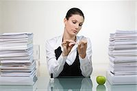A woman in an office doing her nails. Stock Photo - Premium Royalty-Freenull, Code: 6102-03827267