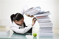A woman in an office with a large pile of paper. Stock Photo - Premium Royalty-Freenull, Code: 6102-03827272