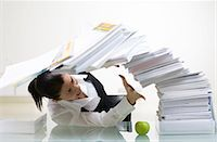 A woman in an office with a large pile of paper. Stock Photo - Premium Royalty-Freenull, Code: 6102-03827273