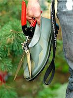 Someone holding a shoe and a pair of pruning shears, Sweden. Stock Photo - Premium Royalty-Freenull, Code: 6102-03827427