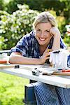 Portrait of a woman doing carpentry in a garden, Sweden. Stock Photo - Premium Royalty-Free, Artist: AWL Images, Code: 6102-03828153