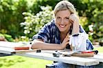 Portrait of a woman doing carpentry in a garden, Sweden. Stock Photo - Premium Royalty-Free, Artist: Ikon Images, Code: 6102-03828154