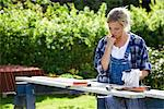 A woman doing carpentry in a garden, Sweden. Stock Photo - Premium Royalty-Free, Artist: Bettina Salomon, Code: 6102-03828155