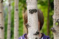Boy Hidden Behind Tree trunk Stock Photo - Premium Royalty-Freenull, Code: 600-03836149