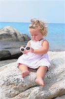 Little Girl with Sunglasses Sitting on Rock Stock Photo - Premium Rights-Managednull, Code: 700-03836230