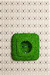 Energy saving electrical wall outlet covered in grass