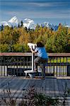 Woman visitor looks through telescope at the southside view of Mt. Mckinley and Alaska Range from the Alaska Veterans Memorial rest area along George Parks Highway, Denali State Park, Southcentral Alaska, Autumn Stock Photo - Premium Rights-Managed, Artist: AlaskaStock, Code: 854-03844969