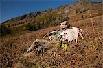 Male moose hunter rests on a sunny mountainside with his trophy moose antler rack in the Bird Creek drainage area, Chugach Mountains, Chugach National Forest, Southcentral Alaska, Autumn Stock Photo - Premium Rights-Managed, Artist: AlaskaStock, Code: 854-03845051
