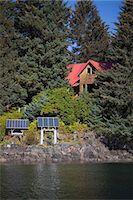 solar panel usa - Scenic view of a log home powered by solar panels in Anton Larsen Bay, Kodiak Island, Southwest Alaska, Summer Stock Photo - Premium Rights-Managednull, Code: 854-03845244