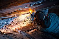 professional (pertains to traditional blue collar careers) - Worker cuts metal fittings off a boat hull using an oxy-acetylene cutting torch, Kodiak Boatyard, Saint Herman Harbor, Kodiak, Near Island, Southwest Alaska, Autumn Stock Photo - Premium Rights-Managednull, Code: 854-03845278