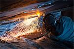 Worker cuts metal fittings off a boat hull using an oxy-acetylene cutting torch, Kodiak Boatyard, Saint Herman Harbor, Kodiak, Near Island, Southwest Alaska, Autumn Stock Photo - Premium Rights-Managed, Artist: AlaskaStock, Code: 854-03845278