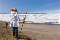 professional (pertains to traditional blue collar careers) - Portrait of a male Inupiaq Eskimo hunter wearing his Eskimo parka (Atigi) and seal skin hat and holding a walking stick at Old Utkeagvik original town site overlooking the Chukchi Sea, Barrow, Arctic Alaska, Summer Stock Photo - Premium Rights-Managednull, Code: 854-03845470