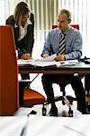 Businessman talking to female colleague as she making notes Stock Photo - Premium Royalty-Free, Artist: Sheltered Images, Code: 632-03848024