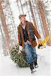 Man with Chainsaw Dragging Christmas Tree Stock Photo - Premium Rights-Managed, Artist: Ty Milford, Code: 700-03849328