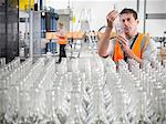 Factory worker examining bottles Stock Photo - Premium Royalty-Free, Artist: Ikon Images, Code: 649-03858190