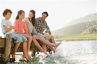 Family on dock splashing feet in lake Stock Photo - Premium Royalty-Freenull, Code: 635-03859690
