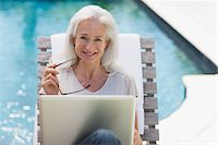 Senior woman using laptop at poolside Stock Photo - Premium Royalty-Freenull, Code: 635-03860443