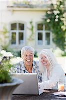 Senior couple using laptop at table in garden Stock Photo - Premium Royalty-Freenull, Code: 635-03860445