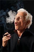 Man Smoking Cigar Stock Photo - Premium Royalty-Freenull, Code: 600-03865037
