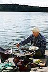 A man barbecuing fish by the water, Sweden. Stock Photo - Premium Royalty-Free, Artist: foodanddrinkphotos, Code: 6102-03867439