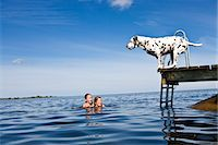preteen girls bath - Dog on a jetty and girls swimming, Oland, Sweden. Stock Photo - Premium Royalty-Freenull, Code: 6102-03867487