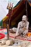 Shivaite Naga sadhu poking a sacred fire in his akhara at the Kumbh Mela in Hardwar, Uttarakhand, India, Asia