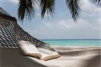 Open book in hammock on beach Stock Photo - Premium Royalty-Freenull, Code: 649-03881537